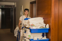 Young man pushing a housekeeping cart in a hotel Stock Photos