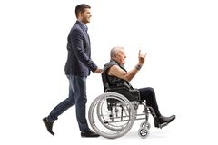 Young man pushing an man in leather vest making a rock and roll hand sign in a wheelchair royalty free stock image