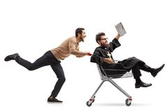 Young man pushing a priest in a shopping cart. Full length profile shot of a young men pushing a priest in a shopping cart isolated on white background royalty free stock photos