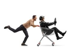 Young man pushing a shopping cart with a biker riding inside Royalty Free Stock Images