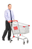 Young man pushing a shopping cart Royalty Free Stock Images