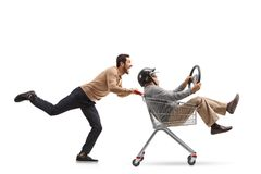 Young man pushing a shopping cart with a mature man with a helme Stock Photo