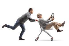 Young man pushing a shopping cart with a mature man riding insid Royalty Free Stock Photos