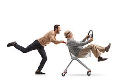 Young man pushing a shopping cart with a mature man riding insid Royalty Free Stock Images