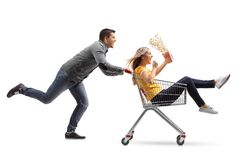 Young man pushing a shopping cart with a woman with a popcorn bo Royalty Free Stock Images