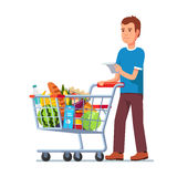 Young man pushing supermarket shopping cart Stock Photo