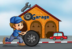 A young man pushing the tire in front of the garage Royalty Free Stock Images