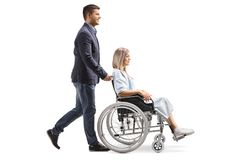 Young man pushing a young woman in a wheelchair. Full length profile shot of a young men pushing a young women in a wheelchair isolated on white background royalty free stock image