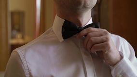 Young man put on bow tie. Steadicam stock video