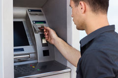 Young man put his credit card at the ATM Royalty Free Stock Photography