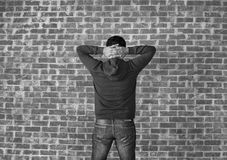 Young man put his hands behind head. Black and white Royalty Free Stock Photography