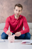 Young man puts savings into piggy bank Royalty Free Stock Photography