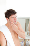 Young man putting aftershave in the bathroom Stock Photo