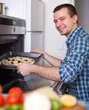 Young man putting a baking sheet with pizza into oven Stock Images