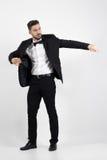Young man putting on black suit tuxedo coat. Full body length portrait over gray studio background Stock Photos