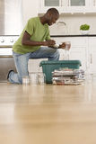Young man putting can and glass jar into recycling bin in kitchen, ground view Stock Photography