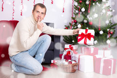 Young man putting christmas present box under christmas tree Stock Photo