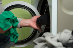 Young Man Putting A Cloth Into Washing Machine Royalty Free Stock Photography