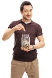 Young man putting a coin into jar with money Stock Photography