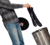 Young man putting dirty socks in a laundry basket Royalty Free Stock Photography