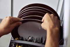 Young man putting a dishwashing machine Royalty Free Stock Photography