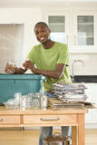 Young man putting empty glass jar and can into recycling bin in kitchen, smiling, portrait. Young men putting empty glass jar and can into recycling bin in Stock Photo