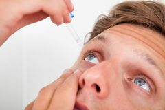 Young man putting eye drops in his eyes Stock Image