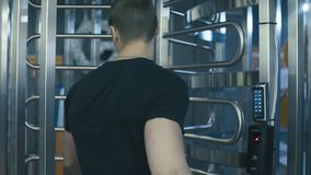 Young man putting finger in biometric lock. Then opening a door in fitness studio stock video footage