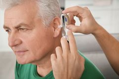 Young man putting hearing aid in father`s ear, closeup. Young man putting hearing aid in father`s ear indoors, closeup stock photo