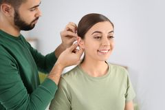 Young man putting hearing aid in woman`s ear. Young men putting hearing aid in woman`s ear indoors stock photo