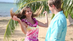 Young man putting lei garland of pink orchids around woman neck at beach. Young couple is enjoying their summer vacation on Oahu Hawaii stock video
