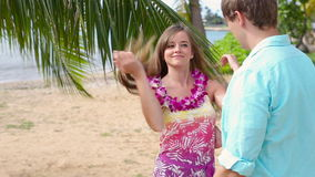 Young man putting lei garland of pink orchids around woman neck at beach. Young couple is enjoying their summer vacation on Oahu Hawaii stock video footage