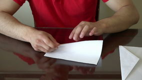 Young man putting a letter inside an envelope stock footage