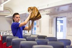 Young man putting luggage into overhead locker at Royalty Free Stock Photography