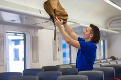 Young man putting luggage into overhead locker at Stock Image
