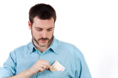 Young man putting money in his pocket Royalty Free Stock Photography