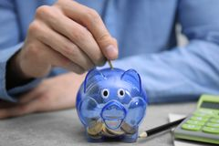 Free Young Man Putting Money Into Piggy Bank Stock Images - 111526544