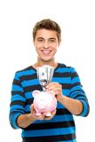 Young man putting money in piggy bank Stock Photos
