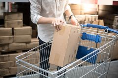 Young man putting paper box into trolley cart in warehouse. Shopping warehousing concept Royalty Free Stock Photo