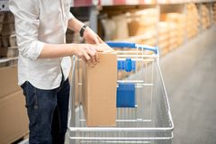 Young man putting paper box into trolley cart in warehouse. Shopping warehousing concept Stock Images