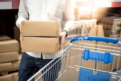 Young man putting paper boxes into trolley cart in warehouse. Shopping warehousing concept Stock Image