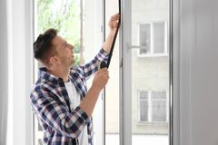 Young man putting sealing foam tape on window. Indoors royalty free stock photos