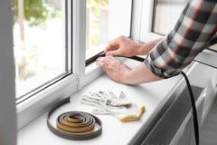 Young man putting sealing foam tape. On window indoors stock photos