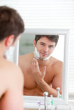 Young man putting shaving foam on his face. Young man putting some shaving foam standing in the bathroom looking at the camera Stock Image