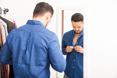 Young man putting on a shirt at home Stock Image