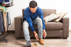 Young man putting shoes on in dressing room Royalty Free Stock Photos