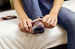 Young man putting on or taking off his socks stock photo