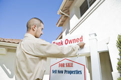 Young Man Putting Up 'For Sale Notice'. Outside the house stock images