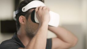 Young man putting on video glasses. Portrait of man sitting in video glasses. stock footage