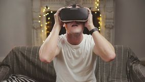 341d00de7021 Young man putting virtual reality glasses on to play video games stock  video footage